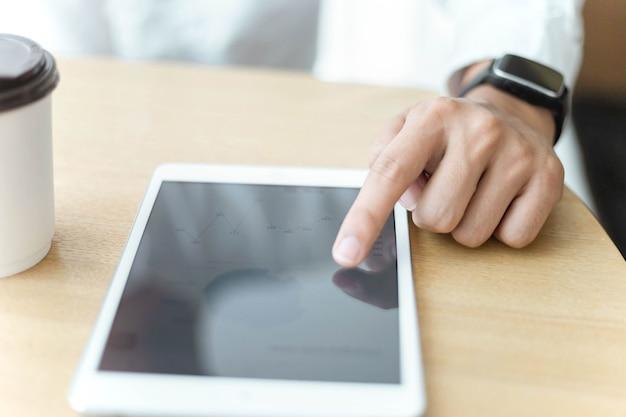 O conceito de empreendedor é uma mão passando na tela do tablet e colocando perto de uma xícara de café.