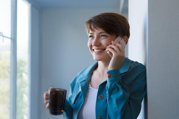 O conceito de emprego, entrevistas, publicidade de tecnologia digital - mulher tomando café e falando ao telefone. mulher sorridente com xícara faz uma ligação. manhã de menina