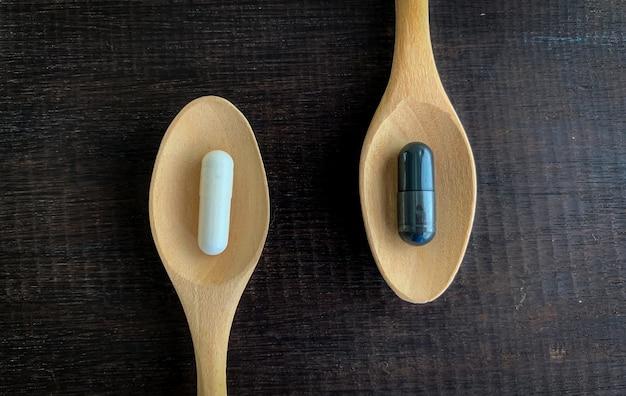 O conceito de escolhas diferentes, pílulas brancas e pílulas pretas são colocadas em uma colher de pau