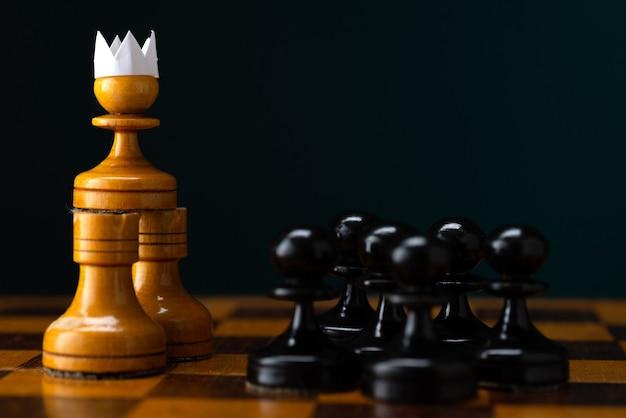 O conceito de estratégia e planejamento de negócios, um peão branco em uma coroa de papel em uma coroa de papel contra um exército de peões negros, estratégia e tática, prontos para a batalha
