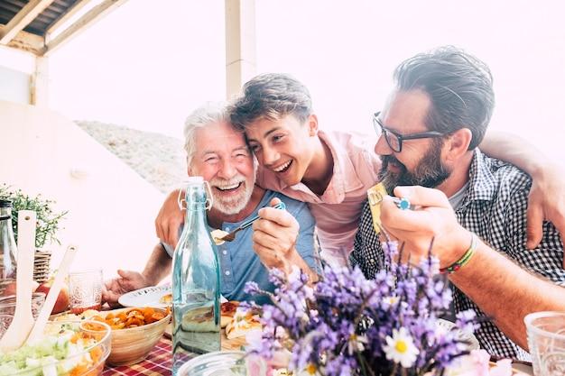 O conceito de família de pessoas felizes ria e se diverte junto com três gerações de idades diferentes: avô, pai e filho adolescente, todos juntos comendo no almoço