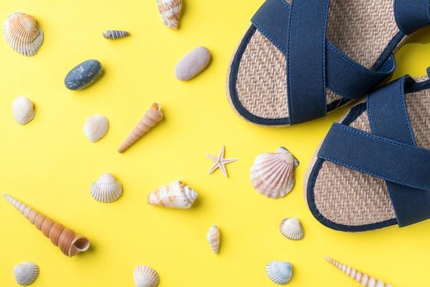 O conceito de férias de verão. conchas de sandálias de verão feminino em fundo amarelo