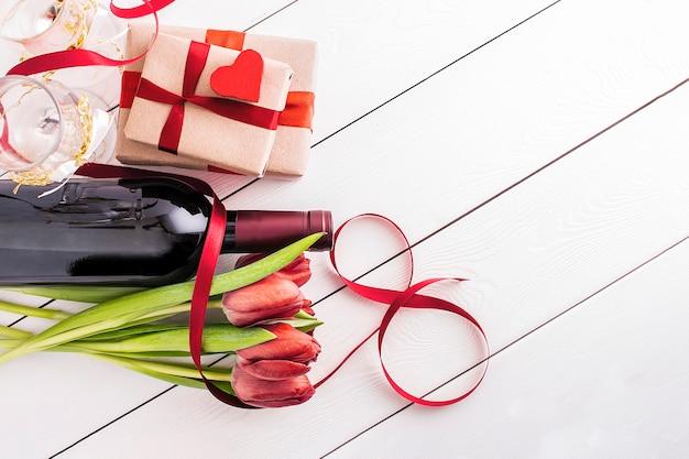 O conceito de férias femininas. tulipas vermelhas com presentes em um fundo branco com cópias do espaço.