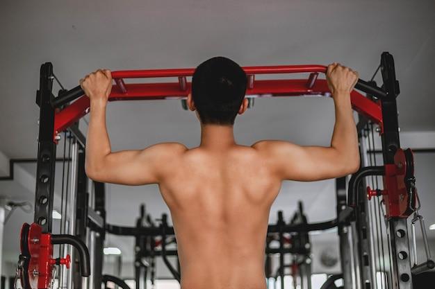 O conceito de ginásio de treinamento é um jovem adulto forte usando as duas mãos fazendo abdominais; puxando-se para cima e para baixo no equipamento de ginástica.