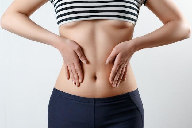 O conceito de gravidez precoce, saúde da mulher. foto de close-up de uma bela barriga esbelta e umbigo de uma mulher.