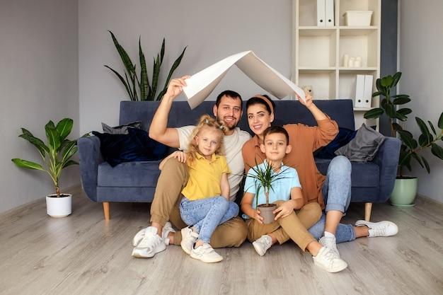 O conceito de habitação para uma jovem família. mãe, pai e filhos em uma nova casa com um telhado na casa