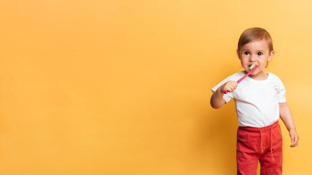 O conceito de higiene dental. uma garotinha loira escova os dentes com pasta de dente. fundo amarelo. um lugar para o seu texto.