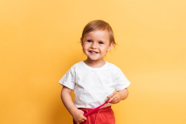 O conceito de higiene dental. uma garotinha loira escova os dentes com pasta de dente. fundo amarelo.