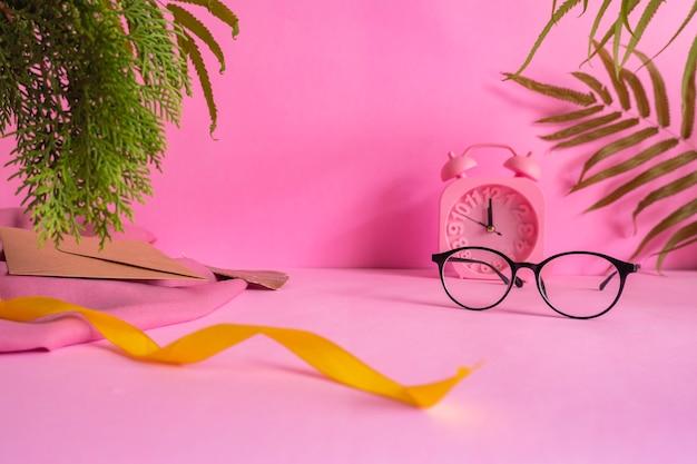 O conceito de ideias de composição com produtos. fundo rosa decorado com óculos, relógio, flores de pinheiro, folhas e tecido