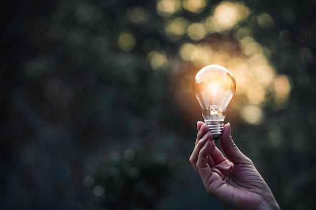 O conceito de inovação e energia da mão segura uma lâmpada e copia o espaço para inserir texto.