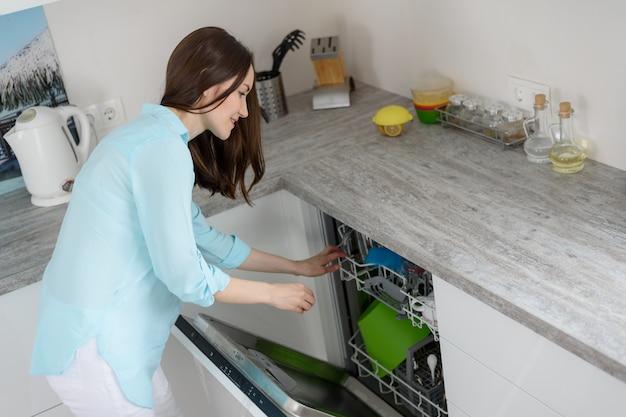O conceito de lavar pratos modernos, uma mulher puxa pratos limpos da máquina de lavar louça na cozinha branca