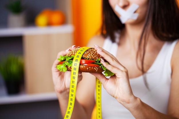 O conceito de mulher de dieta com a boca selada mantém hambúrguer gorduroso