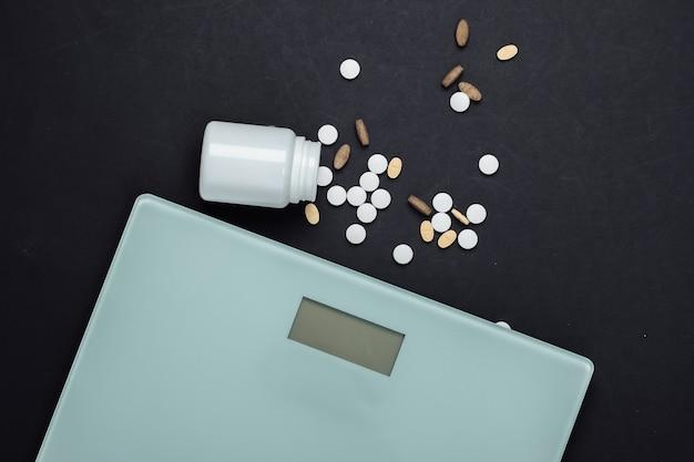 O conceito de perder peso. balança de chão, um frasco de pílulas de vitaminas no preto.
