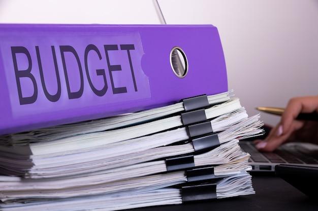 O conceito de planejamento orçamentário em contabilidade. uma mulher de negócios está cercada por grandes pilhas de documentos.