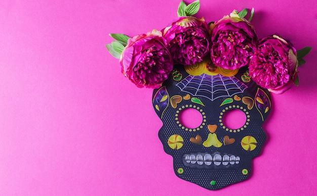 O conceito de plano de fundo do feriado dia de muertos. crânio de máscara festiva preta com flores sobre fundo fúcsia.