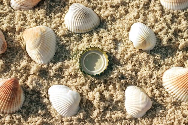 O conceito de poluição do planeta a tampa da garrafa encontra-se entre as conchas na areia