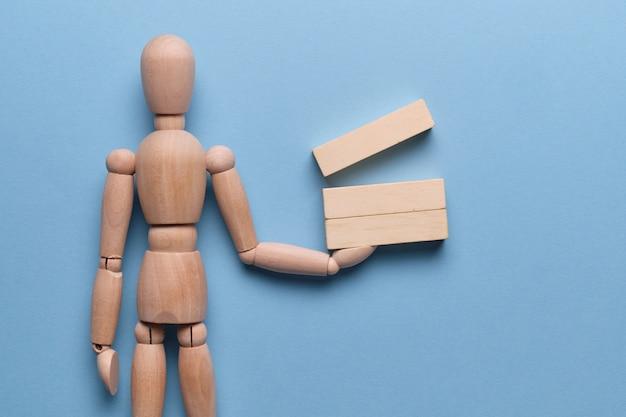 O conceito de preparação de relatórios de negócios. blocos de madeira mantém um manequim em um espaço azul.