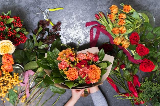 O conceito de presentes e buquês para 8 de março e dia das mães. florista cria um buquê em uma loja de flores