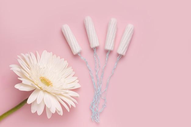 O conceito de proteção durante o ciclo menstrual. tampões ao lado de uma flor
