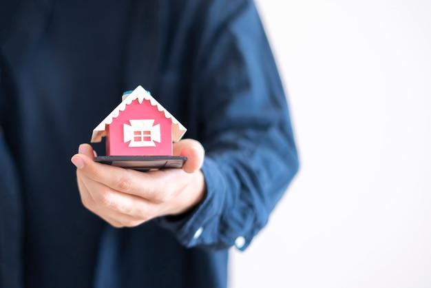 O conceito de seguro de propriedade, as mãos segurando um pequeno brinquedo de casa e proteger o imóvel