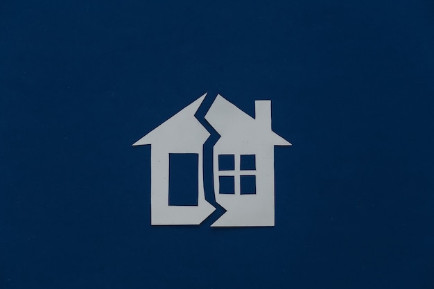 O conceito de separação de propriedade, divórcio. casa de papel cortada ao meio em um azul clássico