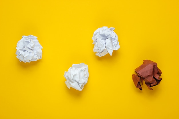 O conceito de singularidade, discriminação racial. bolas de papel amassado brancas e marrons na tabela amarela. vista superior, negócios de minimalismo
