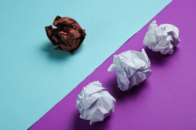 O conceito de singularidade, discriminação racial. bolas de papel amassado brancas e marrons na tabela azul roxa. negócio de minimalismo