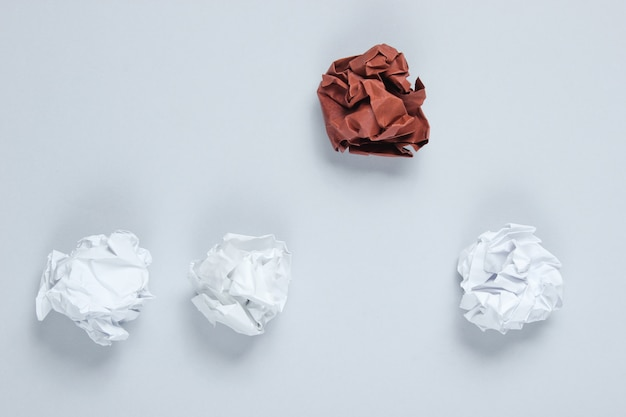 O conceito de singularidade, discriminação racial. bolas de papel amassado branco e marrom na mesa cinza. vista superior, minimalismo