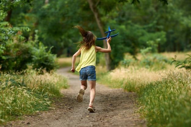 O conceito de sonhos e viagens. garota feliz criança brincando com o avião de brinquedo no verão na natureza.