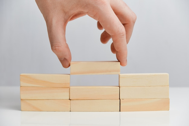 O conceito de tarefas básicas. mão segura blocos de madeira em um espaço em branco.