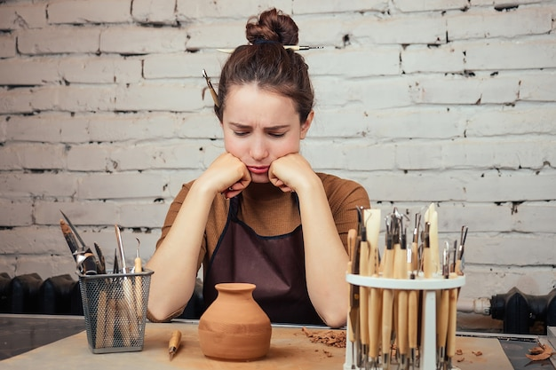 O conceito de tristeza e falta de ideias na criatividade. uma mulher jovem e triste olha para um vaso de barro. o oleiro faz um vaso à mesa de uma olaria.