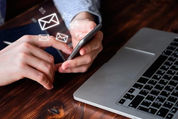 O conceito de troca de emails. um homem trabalha em um smartphone.