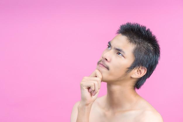 O conceito de um jovem sem camisa, mostrando gestos e rosa.