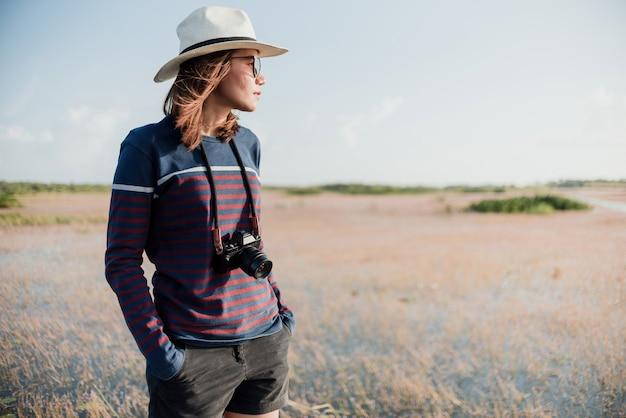 O conceito de um turista fotografando uma mulher asiática, segurando uma câmera no pescoço batedor de carteira de mão olhe para o lado