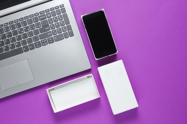 O conceito de unboxing, techno blog. caixa com novo smartphone, laptop na superfície roxa.