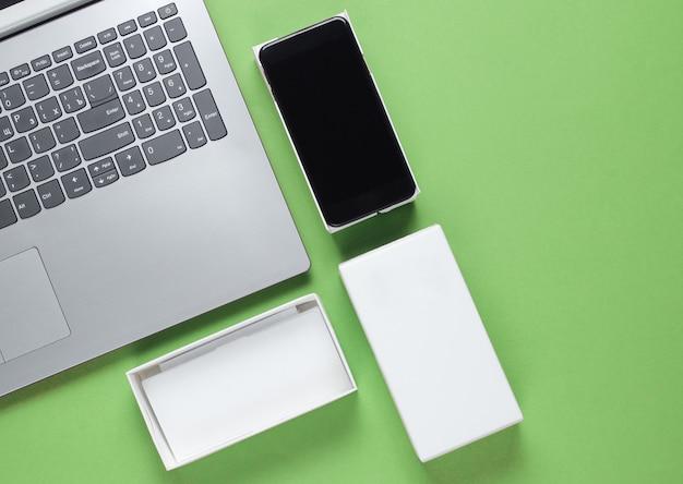 O conceito de unboxing, techno blogging. caixa com novo smartphone, laptop em verde