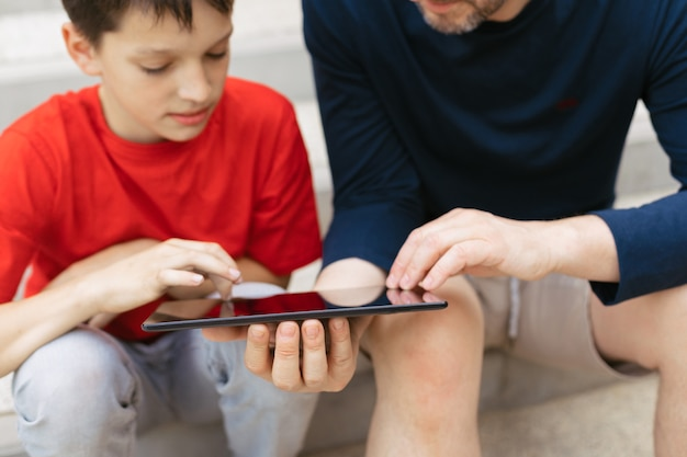 O conceito de usar gadgets para a educação ou passar tempo com crianças. jovem pai e filho nos degraus de uma escada de concreto