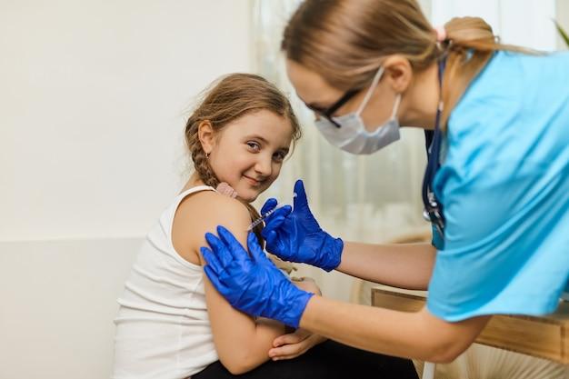 O conceito de vacinação. médica vacinando menina bonitinha na clínica