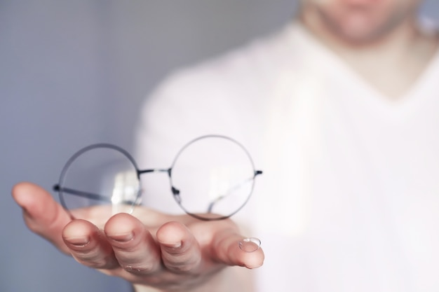 O conceito de visão deficiente. segure uma lente de contato e óculos. um cartaz para publicidade de óculos e lentes.