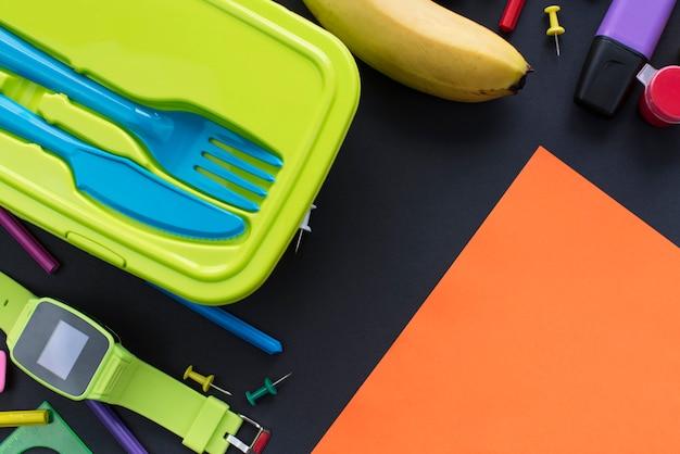 O conceito de volta à escola olha artigos de papelaria da cesta de comida da banana no fundo preto.