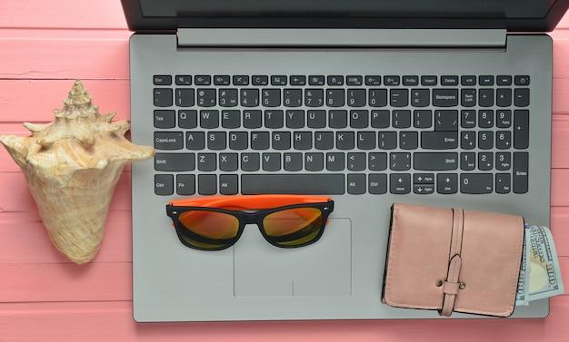 O conceito de web trabalha em um resort de praia, freelancing. laptop, pen drive, óculos escuros, concha, bolsa em uma mesa de madeira de cor rosa. vista do topo.