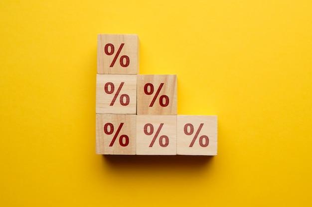 O conceito do crescimento da taxa de juros empresta ícones em blocos de madeira.