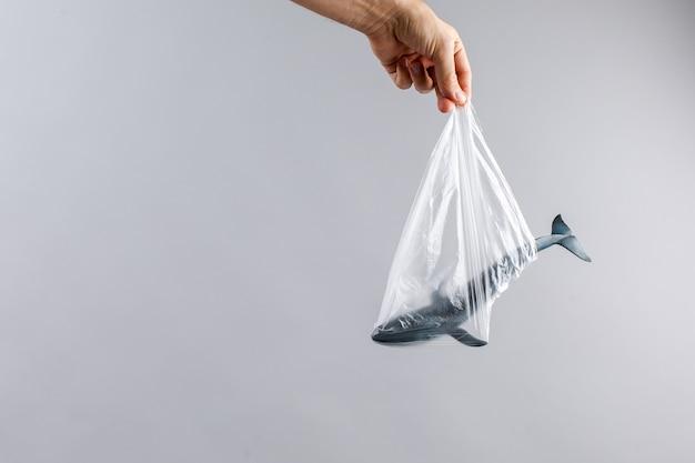 O conceito do dia mundial do meio ambiente. a mão do homem segura a baleia azul em um saco plástico