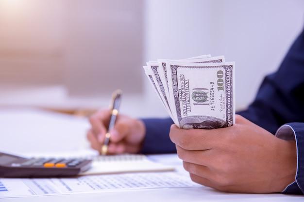 O conceito do dinheiro da economia a mão do homem que põe a fileira e a moeda escreve a finança.