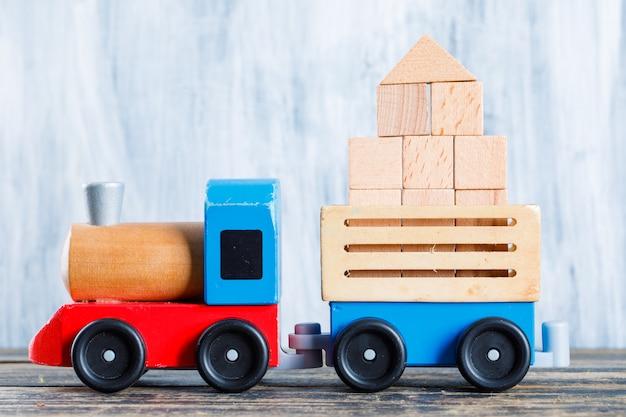 O conceito do jardim de infância com blocos de madeira, criança brinca na opinião lateral do fundo de madeira e sujo.