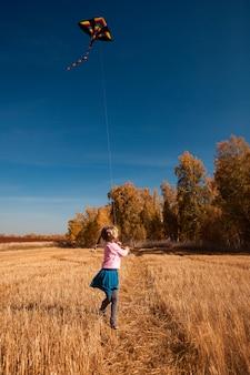 O conceito do livestyle e da recreação ao ar livre da família no outono. uma menina alegre loura aprecia a natureza e joga com um papagaio em um dia ensolarado do outono morno no fundo de um campo e de umas árvores amarelas.