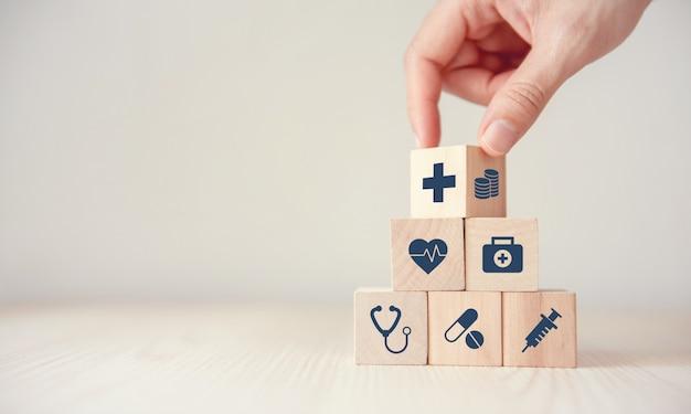 O conceito do seguro de saúde, reduz despesas médicas, cubo de madeira da aleta da mão com os cuidados médicos do ícone médicos e a moeda no fundo de madeira, copia o espaço.