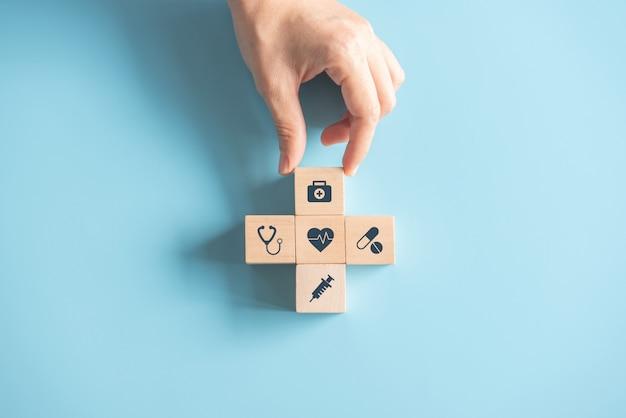 O conceito do seguro médico da saúde, mão que arranja o cubo de madeira com símbolo médico no fundo azul pastel, copia o espaço.