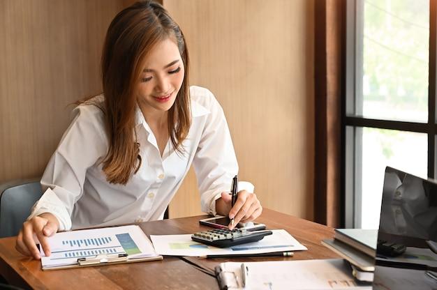 O conceito home da finança, mulher calcula a finança na calculadora.