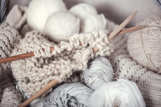 O conceito macro de lã de tricô e agulhas